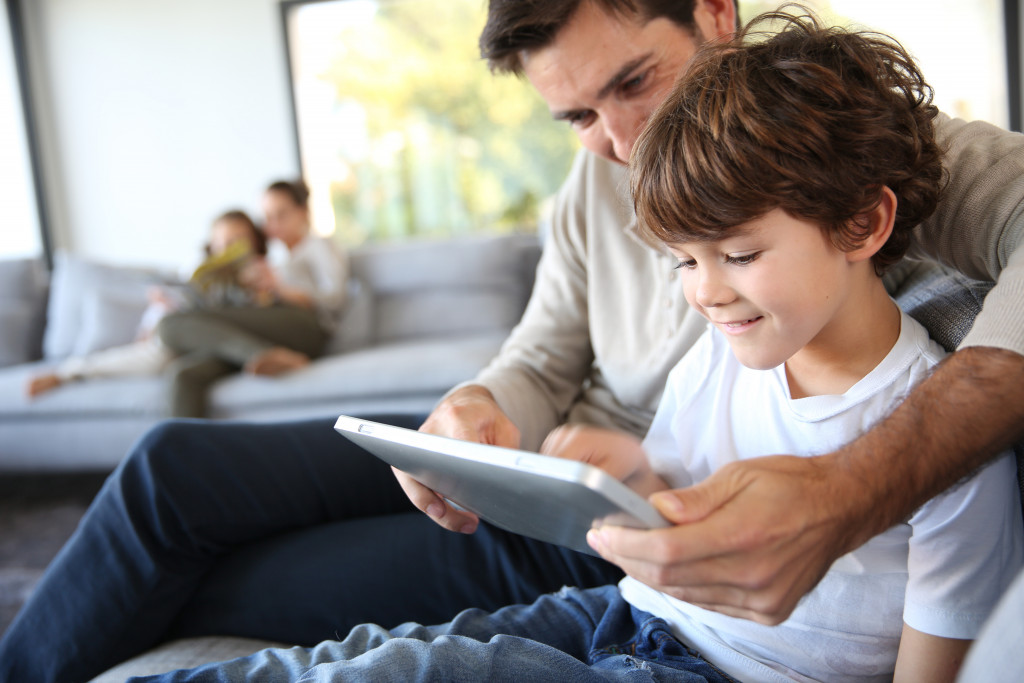 dad reading tablet to kid