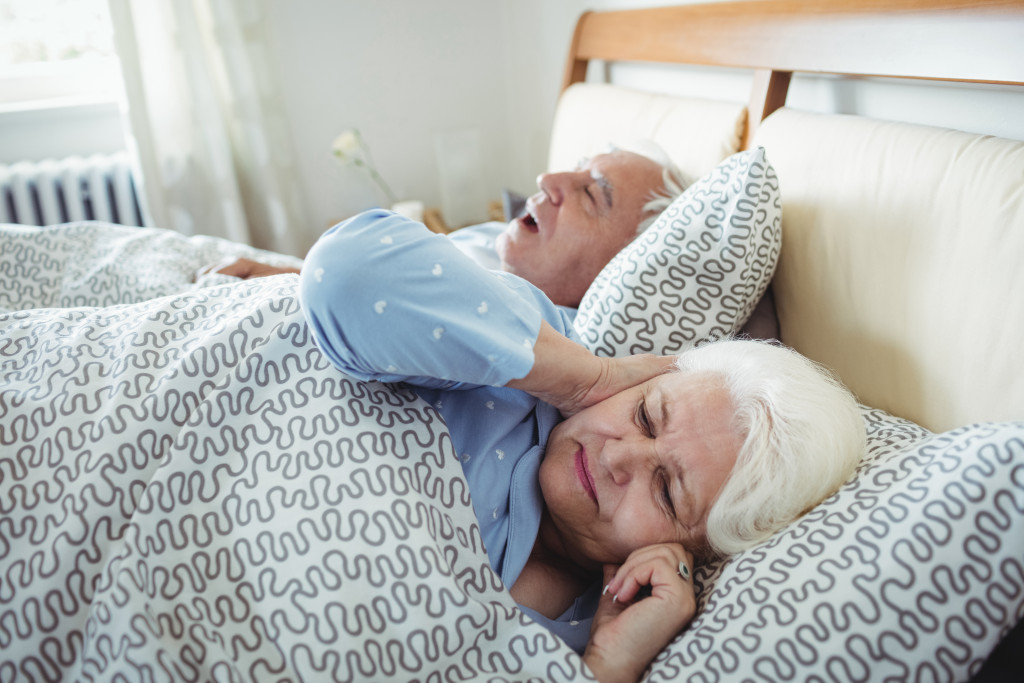 sleeping senior couple with male snoring