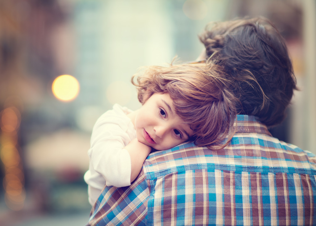 child resting on the shoulder of their dad