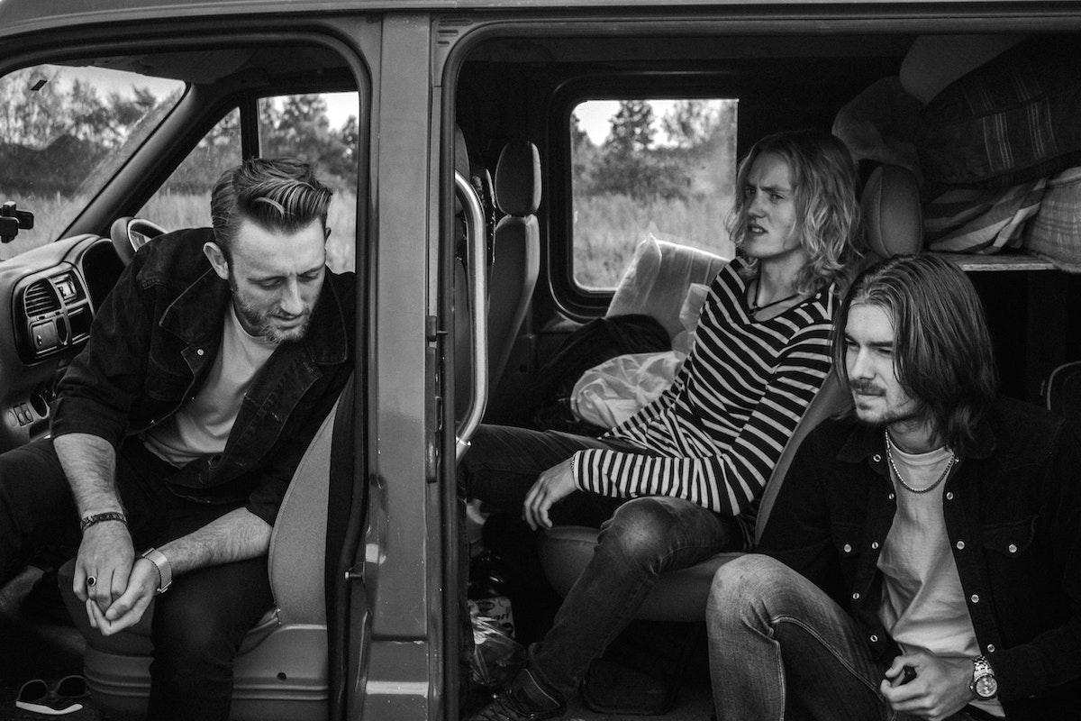 men talking inside a camper van